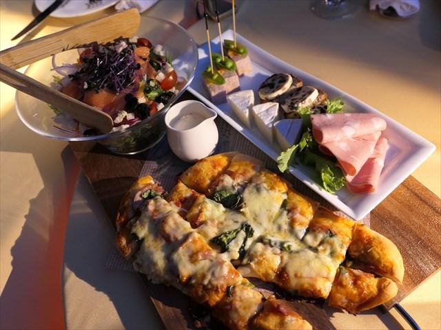 写真:カッティングボードに盛りつけられたピザやチーズ、サラダなど
