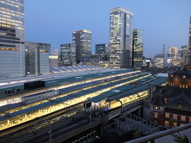 写真:陽が沈み東京駅ホームや高層ビルの灯りが輝き始めるトワイライトタイム