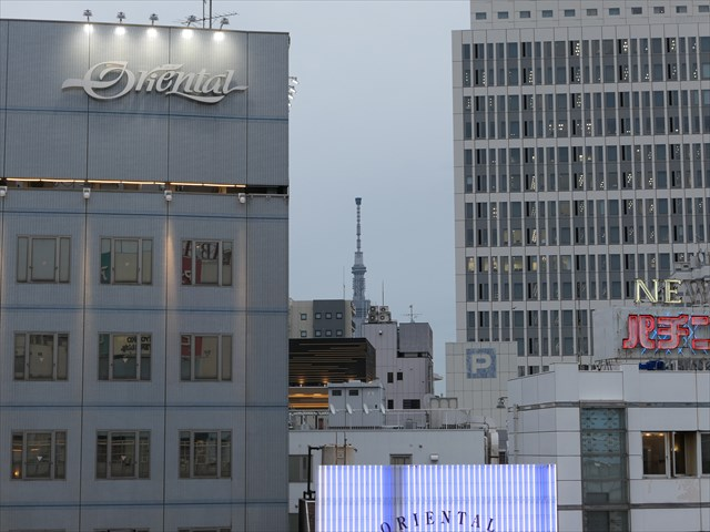 写真:ビルの合間から東京スカイツリーが顔をのぞかせる